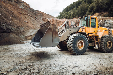 wheel loader machine loading gravel. Industrial machinery working with rock breaker and crusher,...