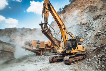 Industrial excavator loading ore and stone material from highway construction site into a dumper truck.
