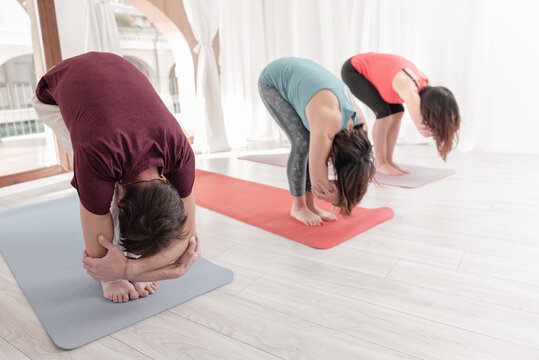 Group of people practicing Yoga. Uttanasana position with elbow grab. Intense stretch pose, forward bend, head to knees. Seguence of Surya namaskar. Greeting to the Sun.