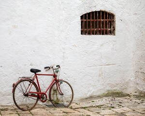 Red bicycle leaned to a white building with a window with rusty balusters