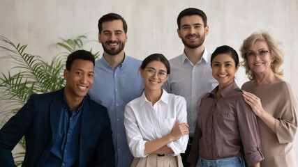 Diverse happy business people successful employees team posing in office, looking at camera,...