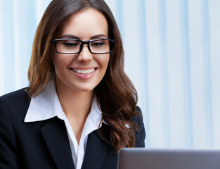 Portrait image of smiling businesswoman in black confident style suit and spectacles, working with laptop computer at office. Success in business, job and education concept.