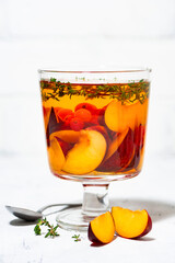 flavored black tea with fresh plums, berries and thyme in glass on white background, vertical