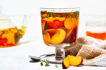 flavored black tea with fresh plums, berries and thyme on white background, closeup