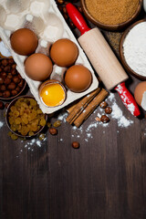 fresh eggs and baking ingredients on wooden table, top view vertical
