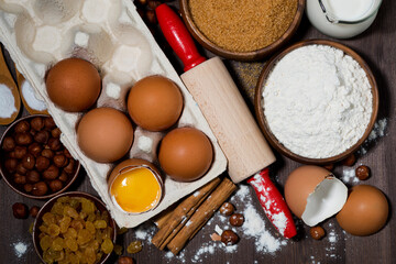 fresh eggs and baking ingredients on wooden table, top view