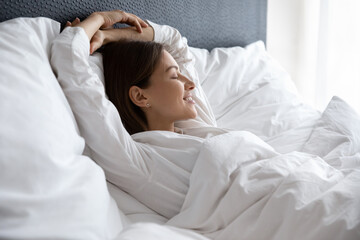Happy millennial female lying resting in comfortable white bed see dreams napping in the morning,...