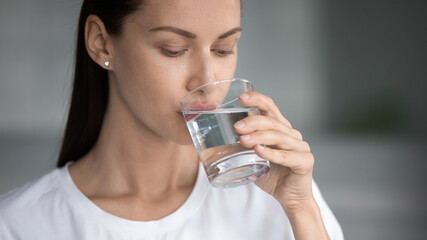 Beautiful millennial woman feel thirsty enjoy still clear mineral water from glass at home, young...