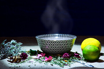 A drinking bowl with hot tea water and lemons and various herbs.