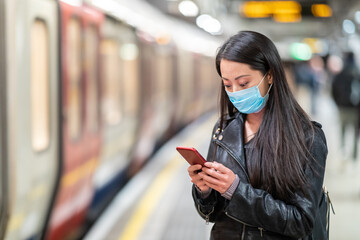 Chinese woman wearing face mask at underground train station and keeping social distance - young asian woman waiting for the train and holding a smartphone - health and travel concepts