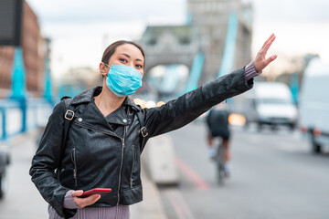Chinese woman in London wearing face mask and hailing a taxi cab - young asian woman next to busy road in the city using a smartphone to book a ride - health and lifestyle concepts