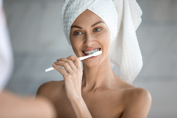 Smiling millennial woman in bath towel after shower look in mirror brush white healthy teeth using...