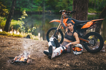 Young female motocross racer wearing motocross outfit with semi naked torso, warming up while...