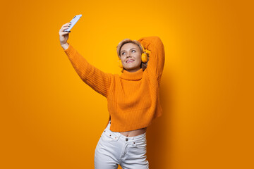 Monochrome photo of a blonde woman with yellow sweater wearing headphones making a selfie on a...