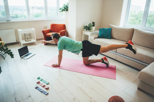 Side view photo of a caucasian man in sportswear stretching on the floor using a laptop and carpet at home