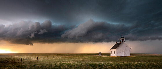 Old church in the rural countryside with a sever storm at sunset. There is an outhouse visible in the scene as well as a green and yellow grass meadow.