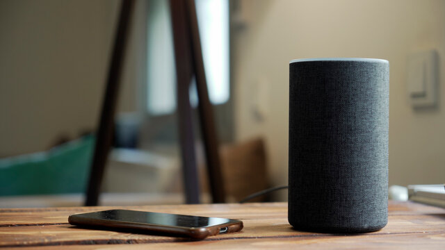 Dark grey Black Amazon Alexa Echo and smart phone on the wooden table in a living room,