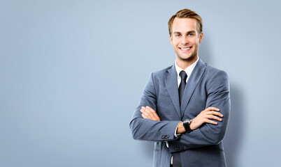 Portrait image of happy smiling confident businessman in grey suit, standing in crossed arm pose, against grey background with copy space for some text. Business success concept picture.