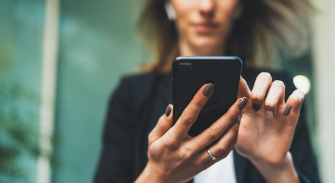 Beautiful young business woman looking at her smart phone near corporate building. close-up of hands of a girl who writes a message in a mobile phone, empty space for text..