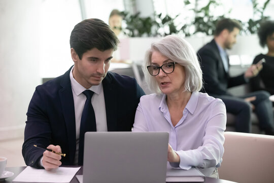 Mature businesswoman use laptop to discuss information with younger colleage. Experienced business woman mentor explain strategy to young manager. Two businesspeople work with online data together