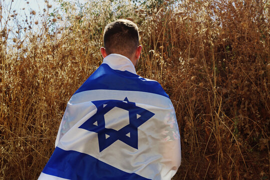 Jewish young  man stands an Israeli field with the flag of Israel on the back. Concepts: patriotic holiday - Independence Day of Israel (from Hebrew: Yom Haatzmaut ) and youth patriotism in Israel