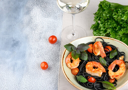Black plate with black Nero spaghetti with langoustines, cherry and garlic, green lettuce leaves and cherry tomatoes