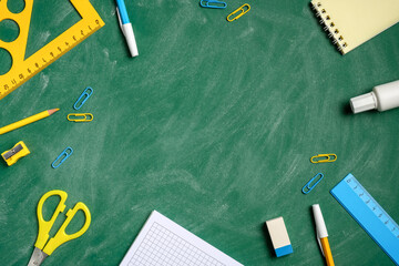 Back to school background with office stationery on green chalkboard table. Top view, flat lay,...