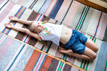 Caucasian girl with braids in a white T-shirt is doing yoga, stretching at home on a striped fabric rug.Digital detox, reunion with nature, healthy break.Doing sports at home, lifestyle.
