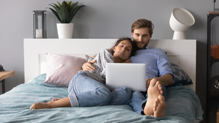 Young man and woman hugging, relaxing, lying in cozy bed in bedroom, using laptop, looking at...