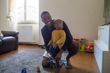 Father sitting on the floor at home putting on shoes on his baby toddler - Single parent changing clothes to his baby - daily routine, bonding, family concept