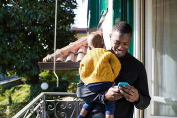 Daddy holding his child in his arms using smartphone - Single parent watching video taking care of his toddler - technology, streaming, family concept