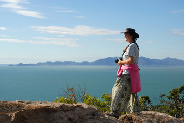 Woman standing on granite boulders at the summit of The Forts Walk, looking out to sea with Cape Cleveland on the horizon, Magnetic Island, Queensland, Australia