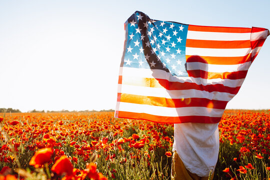 A man with flag of the United States on a shoulder in beautiful poppy field on a clear, sunny day. Celebrating Independence Day, National holiday concept.