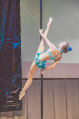 Picture of girl in light blue costume is showing acrobatic ticks on pylon. Straight legs above the head, as activity during quarantine. Little girl on championship on pole dance art.