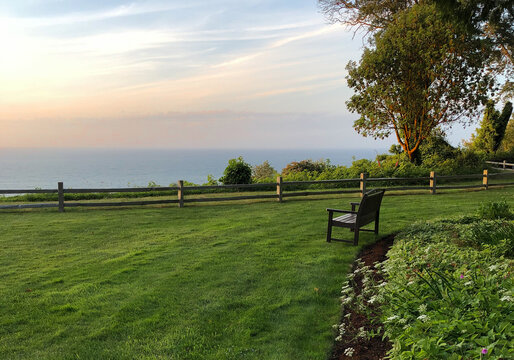Empty bench on manicured green lawn overlooking Puget Sound during pastel sunset