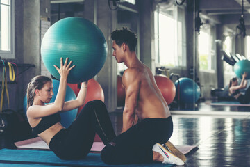 Trainer training yoga ball and exercise with  woman at the gym for healthy care and body slim.