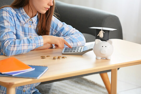Teenage girl with savings for education and calculator at home
