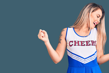 Young beautiful blonde woman wearing cheerleader uniform dancing happy and cheerful, smiling moving...
