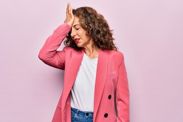 Middle age beautiful businesswoman wearing jacket standing over isolated pink background surprised with hand on head for mistake, remember error. Forgot, bad memory concept.