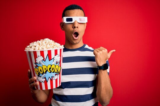 Young handsome african american man watching movie using 3d glasses eating popcorns Surprised pointing with hand finger to the side, open mouth amazed expression.
