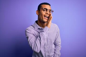 Handsome african american man wearing striped shirt and glasses over purple background hand on mouth telling secret rumor, whispering malicious talk conversation