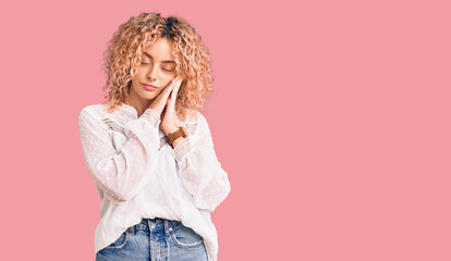 Poster Akt Young blonde woman with curly hair wearing elegant summer shirt sleeping tired dreaming and posing with hands together while smiling with closed eyes.