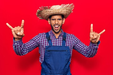 Young latin man wearing farmer hat and apron shouting with crazy expression doing rock symbol with hands up. music star. heavy concept.