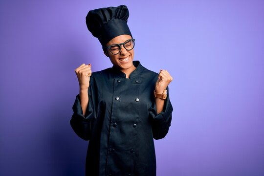 Young african american chef girl wearing cooker uniform and hat over purple background very happy and excited doing winner gesture with arms raised, smiling and screaming for success. Celebration