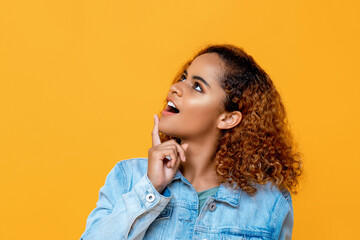 Close up side view portrait of curious young beautiful African American woman looking up while touching her chin with finger in isolated studio yellow background
