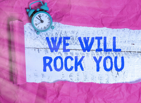 Word writing text We Will Rock You. Business photo showcasing to be going out and facing the world and all that is in it Rolled ripped torn cardboard placed above a wooden classic table backdrop