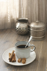 Coffee with cinnamon and silver utensils