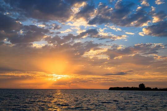 Shot of a wonderful sunset with the sun behind the clouds over sea with calm waves