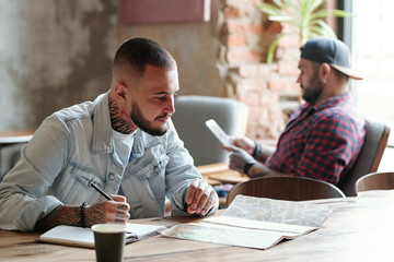 Focused young bearded man sitting at table in cafe and choosing places on paper map while planning vacation