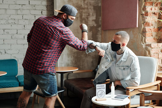 Hipster young friends in masks touching elbows instead of handshake during coronavirus while meeting in lobby